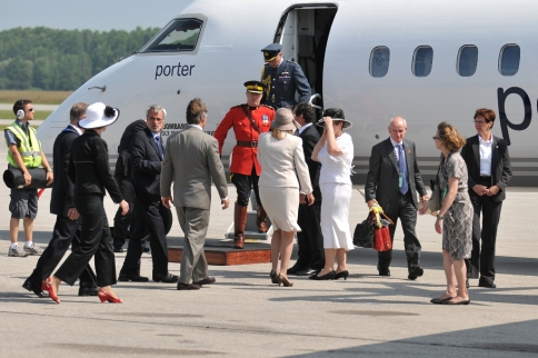 Note the royal purse holder on the right and the airport employee with a roll of red carpet.